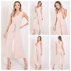 Sleeveless, cropped front knot jumpsuit in pink.